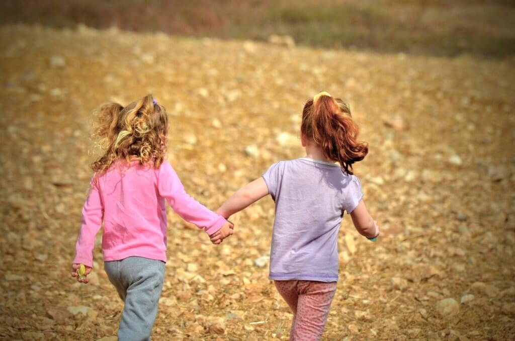Two girls holding hands in friendship