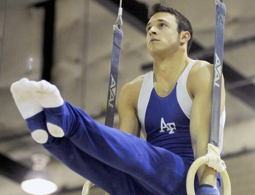 Man performs pike on rings showing that core strength is one of the benefits of gymnastics